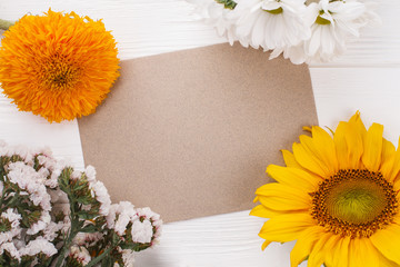 Old beige paper and variety of flowers. Space for your text. White wood background.