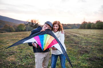 Senior man and a woman holding a kite in an autumn nature at sunset.