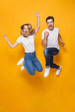 Young loving couple jumping isolated over yellow wall background.