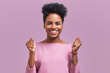 Portrait of overjoyed female clenches fists with with happiness, opens mouth widely as shouts loudly, celebrates her success, poses against lavender background. People, happiness, success concept