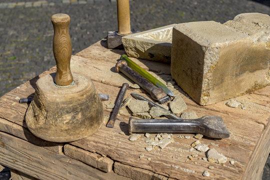 Stonemason tools hammer and chisel outdoors.