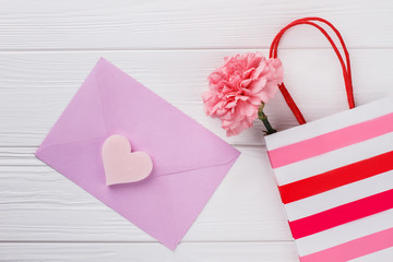 Purple envelope, shopping bag and flower. Romantic concept. White wooden background.