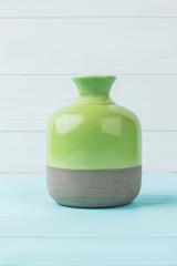 Two-tone vase on wood. Ceramic vase on blue wooden table, white background.