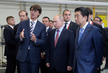 Russian President Putin and Japanese PM Abe listen to Sollers CEO Shvetsov during a visit to the Mazda Sollers Manufacturing Rus joint venture plant of Sollers and Japanese Mazda in Vladivostok