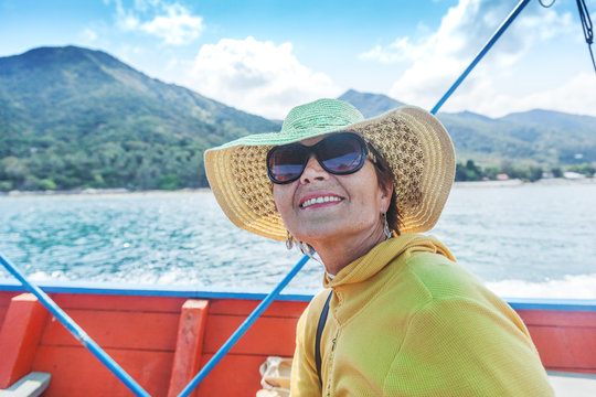 Attractive mature woman of 50 years in a hat and sunglasses on a boat trip on the tropical islands, active seniors