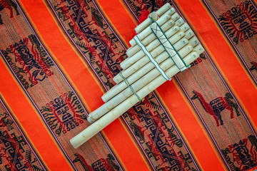 Pan flute on traditional andean fabric background