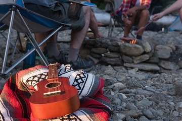 Guitar on picnic blanket at campsite