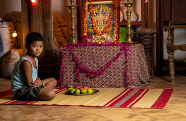 A Nepali boy at an altar (Staged)
