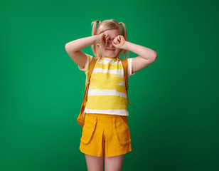pupil with backpack against green background crying