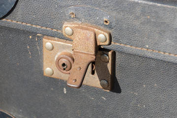 A close up front view of an old rusted travel suitcase lock