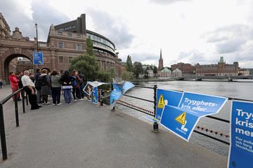 People stand next to election posters near the Swedish parliament in Stockholm