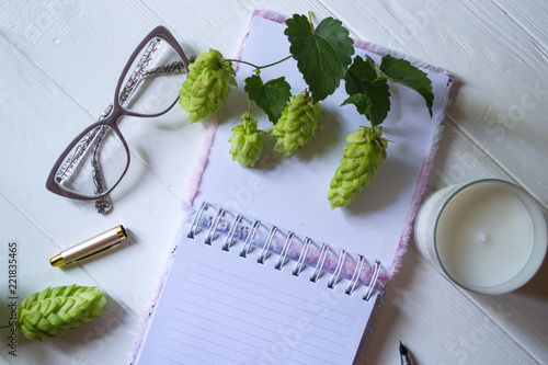 The Opened Notepad Pen White Candle Glasses And Branches Of Hops