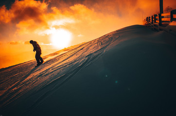Fototapeta Snowboarder in winter ski resort. Sunset in background obraz