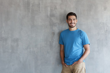 Indoor photo of handsome European guy pictured isolated against grey textured wall standing in blue T-shirt and trousers leaning to wall with shoulder, feeling confident and happy, enjoying free time