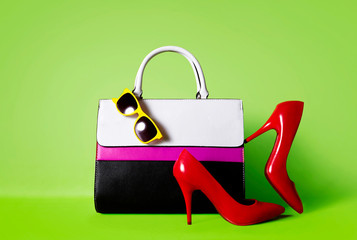 Wall Mural - Colourful handbag, red heels, and yellow sunglasses isolated on green background. Woman shopping image.