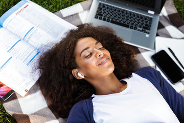 African young woman lies outdoors in park listening music with earphones.