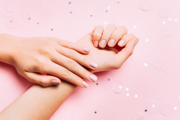 Beautiful woman manicure on creative pink background. Minimalist trend.