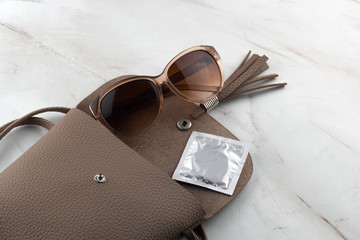 top view of a condom  and sunglasses in an open bag on the marble table
