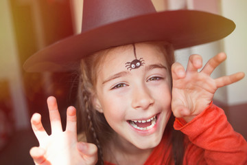 preparation for Halloween. child in a witch outfit doing face painting. cute spider. idea of simple suit, diy Wall mural