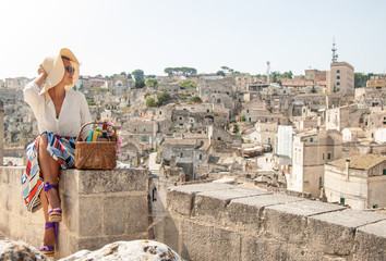 Young elegant woman tourist sitting in historical Matera town in Italy looking at city landscape