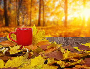 Autumn leaves and hot steaming cup of coffee.