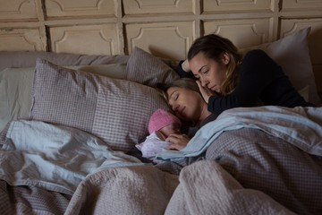 Lesbian couple with baby relaxing on bed