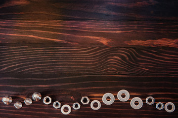 washers, nuts and bolts on wooden table.