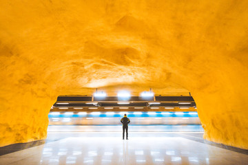 Man standing in modern subway station watching trains pass by during rush hour