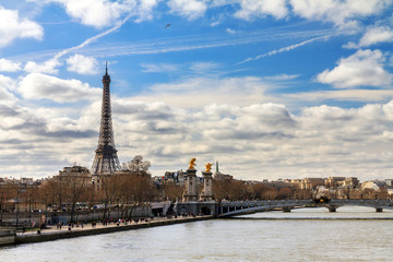 Beautiful view of the river Seine in Paris, with the Eiffel tower in the background, on a cloudy winter day
