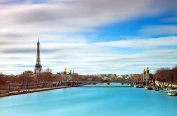 Beautiful colored long exposure view of the river Seine in Paris, with the Eiffel tower in the background, on a cloudy winter day