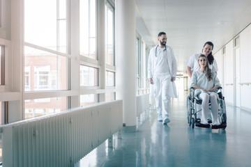 Arzt, Krankenschwester und Patientin in Rollstuhl im Krankenhaus