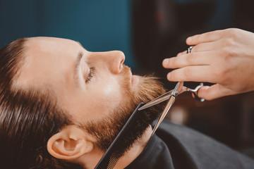 Man hipster having barber shave barbershop scissors.
