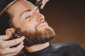 man applying oil to beard article on how to apply beard oil