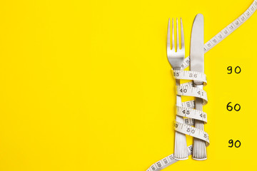 Knife and work with centimeter on yellow background