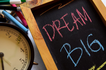 Dream big on phrase colorful handwritten on chalkboard, alarm clock with motivation and education concepts