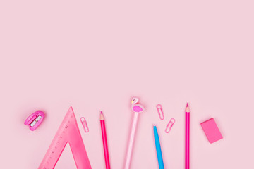 Top view of school supplies on pink pastel background.