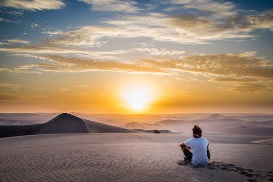 Homme Assis de dos regardant un coucher de soleil à Hucachina au Pérou dans le désert