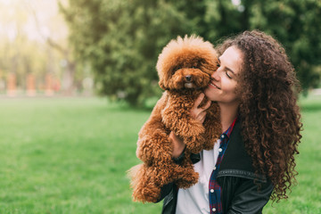 Cool puppy and young woman having fun in park