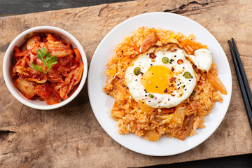 Kimchi fried rice with fried egg on top and fresh kimchi cabbage in a bowl, top view, Korean food