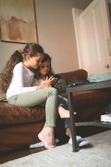 Girls using mobile phone on sofa