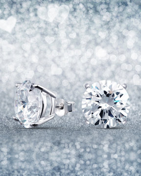 beautiful white diamond stud earrings with reflection on background