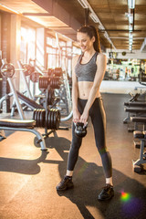 Fit young woman exercising with kettle-bell in gym