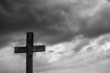Simple oak catholic cross, storm clouds in the background, space for text in black and white.