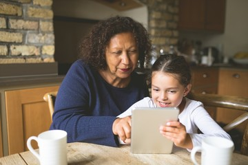 Grandmother and granddaughter using digital tablet in kitchen