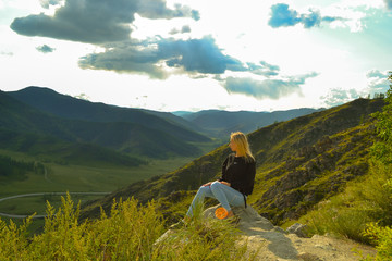 Young pretty blonde woman sit on a rock on a sunny warm autumn summer day resting while traveling near a green tree on the background of landscape and a blue sky with clouds in Altai mountains