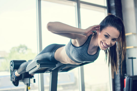 Young fit woman performing back-extension over exercise machine at gym