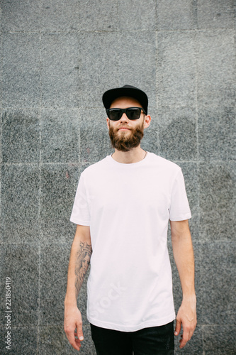 4aa8dc6b7c8c Hipster handsome male model with beard wearing white blank t-shirt and a  baseball cap with space for your logo