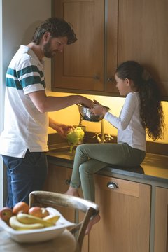 Father and daughter washing vegetable in kitchen