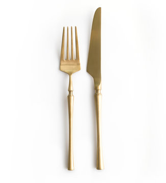 Golden cutlery view from above on a white background. Top view. Knife and fork for a festive table for a wedding, birthday or party.