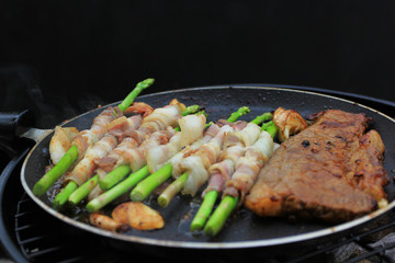 Raw bacon wrapped green asparagus and beef steak in frying pan on dark background